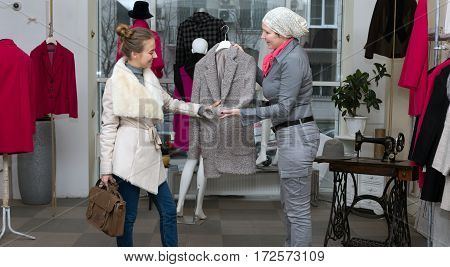 Customer selecting Jacket at Clothing Department Store talking with Saleslady who explains features and trying to convince to make Purchase Shop Interior with many Items and Windows on Background.