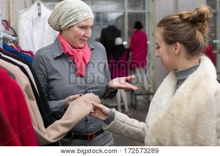 Saleslady in Uniform showing Variety of Winter and Spring Jackets to young Female Customer in Retail Store explaining features and trying to get a deal