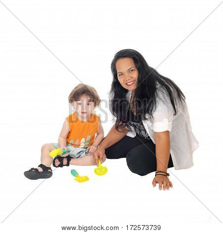 A Filipino nanny sitting on the floor playing with a little three year old boy isolated for white background.
