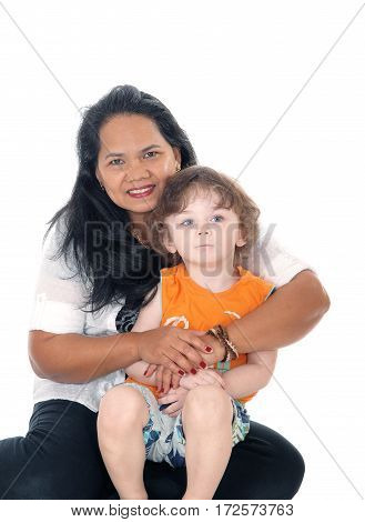 A Filipino nanny taking care of a three year old boy hugging him sitting on the floor isolated for white background.