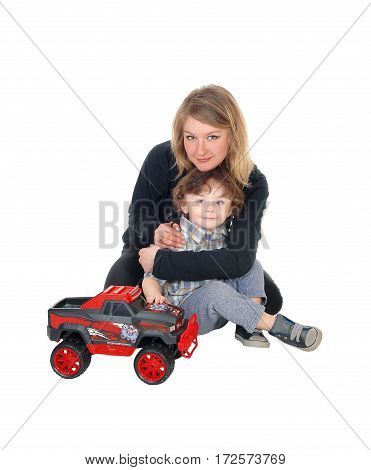 A young mother hugging her little three year old boy sitting on the floor with a red monster truck isolated for white background.