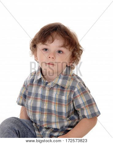 A closeup image of a little three year old boy sitting on the floor looking serious isolated for white background.