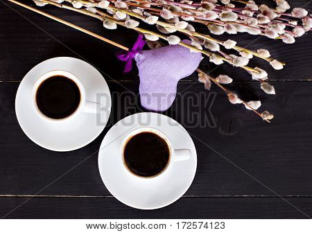 cups of espresso coffee and hearts card on Valentine's Day gift flowers- willow flowers surprise. Dark background space for text.