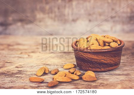 Almond. Almonds in a bowl on the old wooden background.