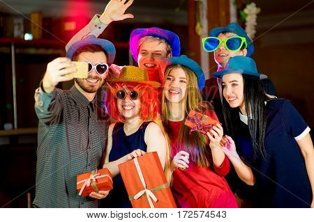 Young peoples birthday party. Gathering a lot of gifts in the nightclub and get selfie