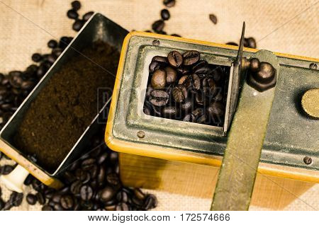 Espresso beans in an old coffee mill on a rustic background vintage color toned