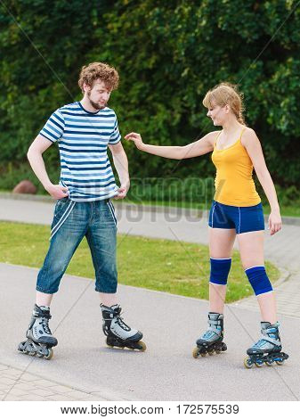 Holidays active people and friendship concept. Young fit couple on roller skates riding outdoors woman and man skating together on city street