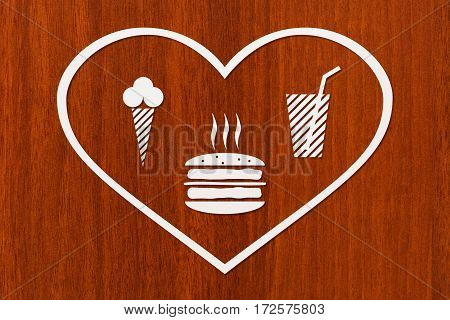 Paper heart with burger beverage and icecream inside on wooden background fastfood concept. Abstract food conceptual image