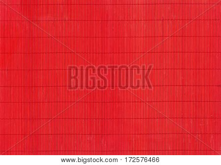 A fragment of the red mat of interwoven chips of bamboo as background