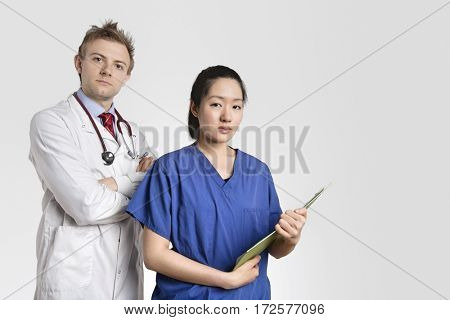 Portrait of a Caucasian doctor standing with an Asian nurse over gray background
