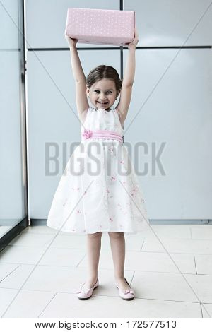 Young girl holding gift wrapped box above her head
