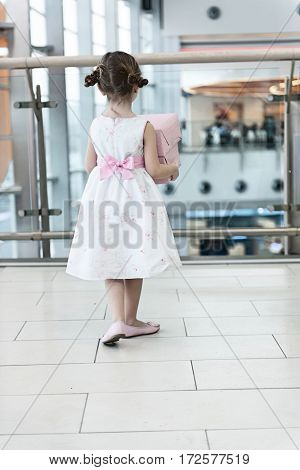 Young girl holding gift wrapped boxes walking away from camera