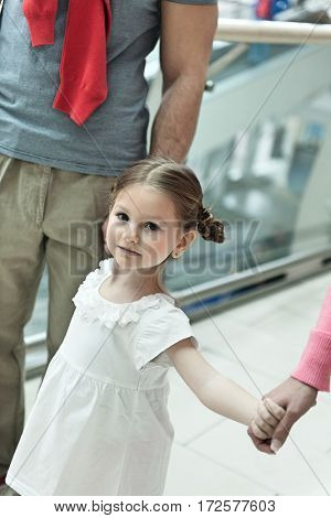 Close-up of young girl holding parents hands