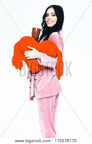 pretty cute sexy girl or beautiful woman with fashion makeup on smiling happy face and curly hair posing in womans pink velour pajama home suit with cup and pillow heart isolated on white background
