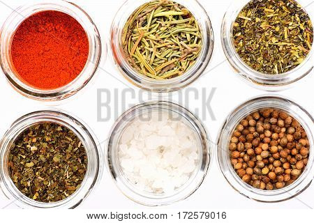 Different Colorful Spices In Glass Jars Isolated On White