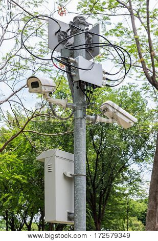 New cctv set with the connection unit on the metal pole in the urban park.