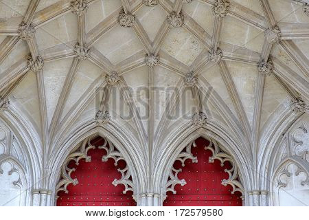 WINCHESTER, UK:  Detail of the main entrance to the Cathedral with red doors and arches