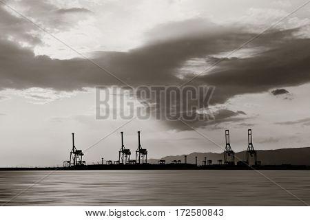 Osaka seaport with crane silhouette at sunset. Japan.