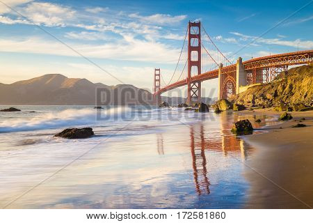 Classic panoramic view of famous Golden Gate Bridge seen from scenic Baker Beach in beautiful golden evening light on a sunny day with blue sky and clouds in summer San Francisco California USA