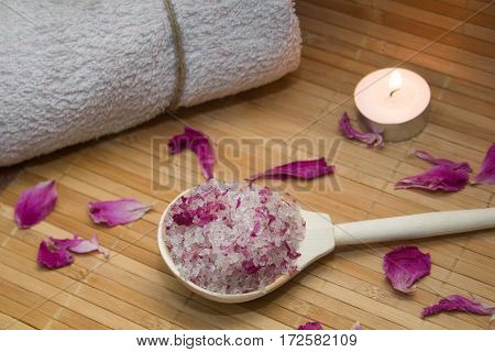 homemade body scrub from sea salt and rose petals and peony candlepink towel on a straw Mat. Spa concept