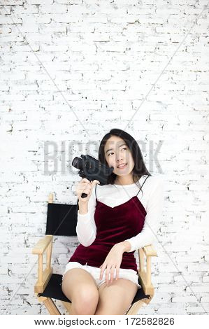 Portrait of Young cute Asian girl having fun recording by camcorder at home