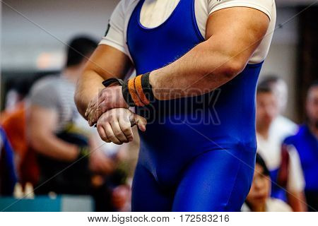 male hands athlete powerlifter with wristbands competition bench press