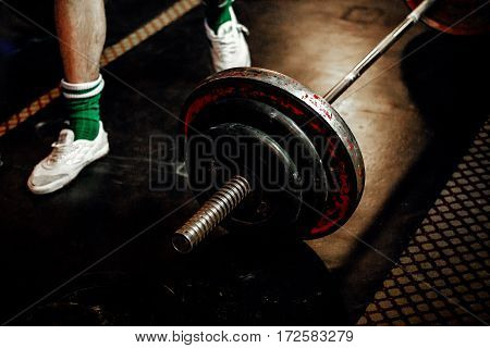 feet male athlete powerlifter and barbell dark floor