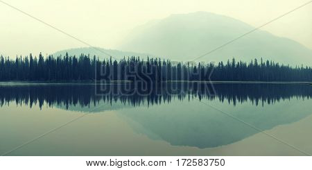 Mountain and forest over lake with reflections in a foggy day.