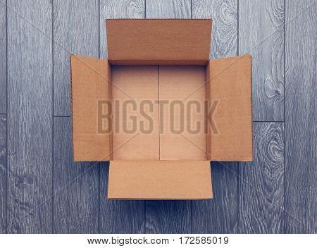 Flat lay of empty open cardboard box on wooden surface