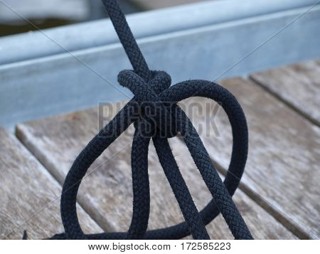 Black marine rope ties off a sail boat that is hanging in its sling in dry dock.