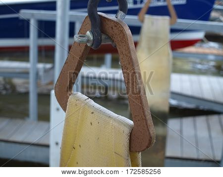 Wood sling holder with sling attached in a slip for a dry docked sail boat.