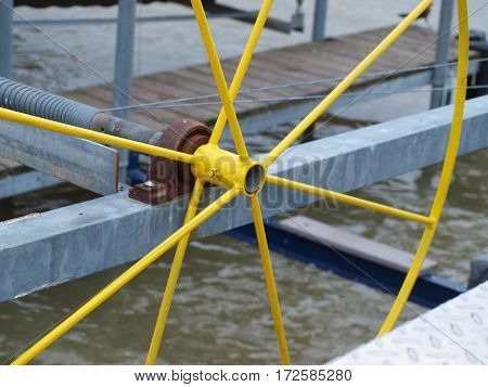A colorful yellow slip wheel is mounted in a sail boat slip with visible upgrades to the mechanics of lifting boats out of the water.