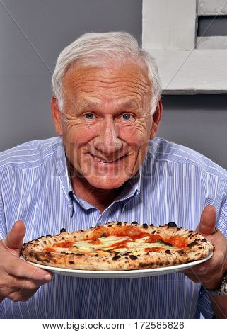 Happy grandfather holding a pizza dish.