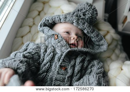 Small baby in knitted clothes lying in the room