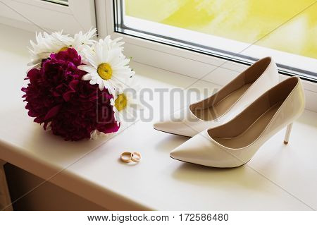 Wedding bouquet of white and purple flowers lay on the window. Morning of the bride the groom's fees. Rings lie on the windowsill. Women's shoes.