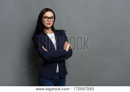 Beautiful young caucasian businesswoman studio shot on grey background. Charming and confident serious brunette woman in casual dark blue jacket wearing glasses