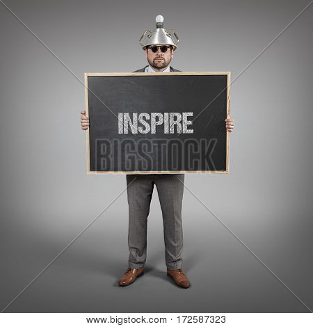 inspire text on blackboard with science businessman holding blackboard sign