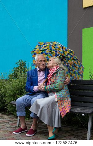 Elegantly dressed elderly couple sitting on a bench under an umbrella. Woman looks at the sky.