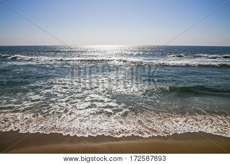 Early morning blue sky and sunlight reflecting of sea with waves breaking on shoreline