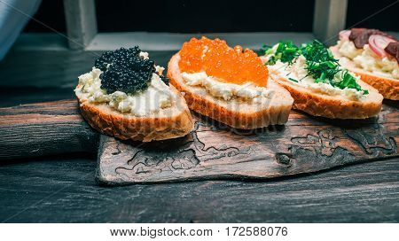 Sandwiches of bran bread with farmer cheese. Assortment of toppings. Served on rustic wooden board