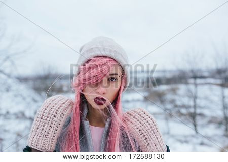 girl with pink hair posing at the camera in winter outdoors