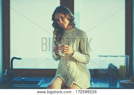 Portrait of a woman holding a cup of tea in her kitchen