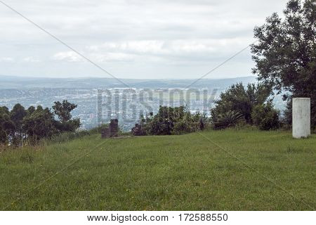 High green lawn viewpoint overlooking a hazey Pietermaritzburg city skyline and overcast sky in South Africa
