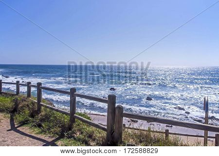 Wooden Barrier along walkway against beach sea and blue sky landscape