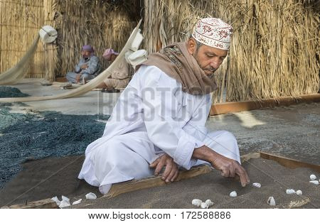 Muscat Oman February 4th 2017: omani men playing hawalais game with shells