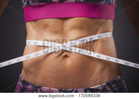 Fitness woman measuring her waist by measure tape