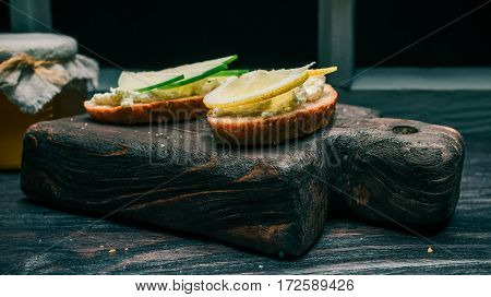 Toasts of bran bread with farmer cheese with apple and lemon toppings. Honey on the background