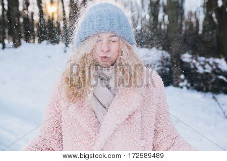 Girl in a knitted cap and gloves playing with snow
