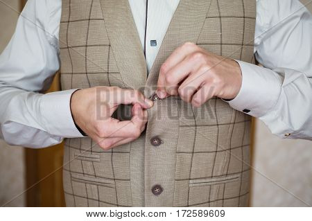 Man buttoning his waistcoat on. Men's style. Professions. Preparing to work on an appointment.