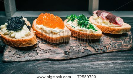 Sandwiches of bran bread with cottage cheese. Toppings of caviar and vegetable. Served on rustic wooden board